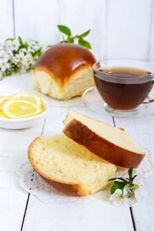 Чашка чая с мягкой булочкой и дольками лимона - хорошее начало дня. завтрак.