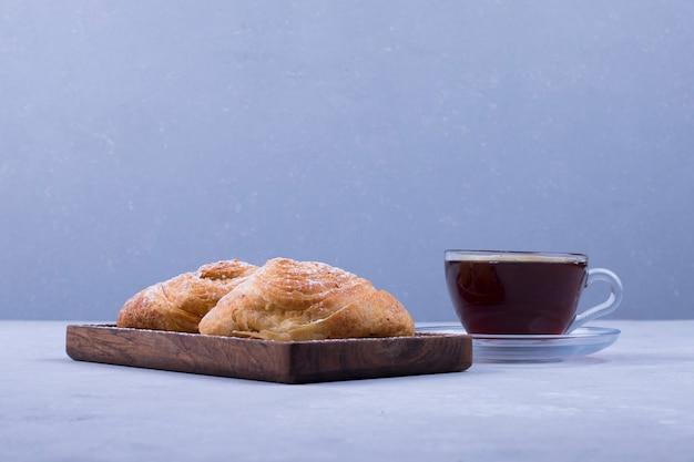 白い木製の背景のプレートにバダンブラとお茶のカップ