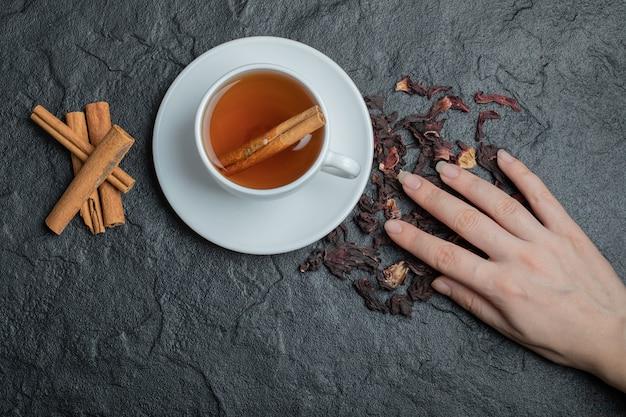 Чашка чая с палочками корицы и настоем.