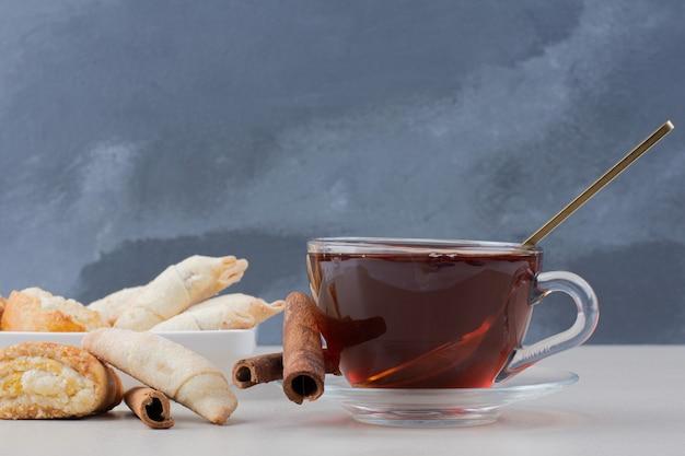 계 피와 흰색 테이블에 쿠키와 차 한잔.