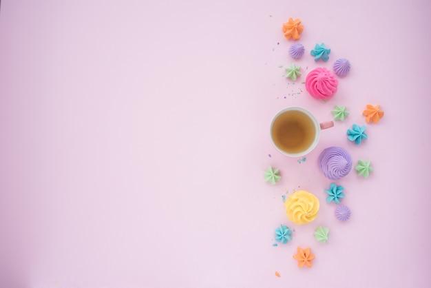 Чашка чая с воздушным воздушным зефиром. мокап для разных идей. пустое место для позитивного, эмоционального текста, прекрасных цитат или высказываний на пастельно-розовом столе. вид сверху