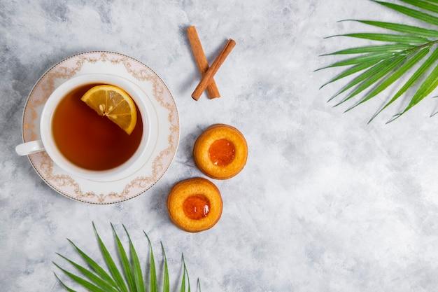 Чашка чая с домашним печеньем с абрикосовым джемом.