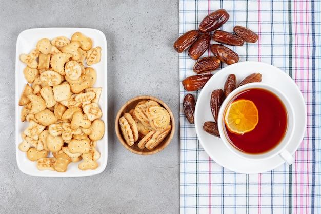 Чашка чая с лимоном и пучок фиников на полотенце рядом с бисквитными чипсами в миске и тарелка на мраморном фоне. фото высокого качества