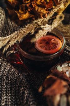 レモンと乾燥した植物がニット生地の上に横たわっているお茶のカップ秋の居心地の良い家の静物