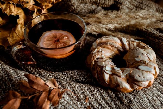 レモンと甘いペストリーとアーモンドがニット生地の上に横たわっているお茶のカップ秋の居心地の良い家