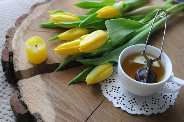나무 테이블에 노란색 튤립과 차 냄비와 차 한잔. 침대에서 아침 식사