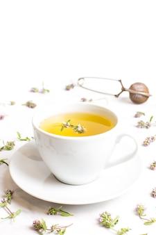 흰색 바탕에 백 리 향 꽃과 차 한잔. 민간 의학의 개념.