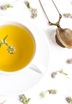 흰색 바탕에 백 리 향 꽃과 차 한잔. 상단에서보기. 민간 의학의 개념.