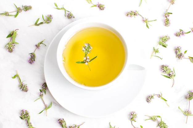 흰색 바탕에 백 리 향 꽃과 차 한잔. 상단에서보기. 민간 의학의 개념. 프리미엄 사진