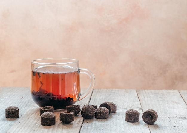 나무 테이블에 오래된 puerh 차 벽돌이있는 전통적인 중국 puer 차 한잔, pu-erh sachets 양조