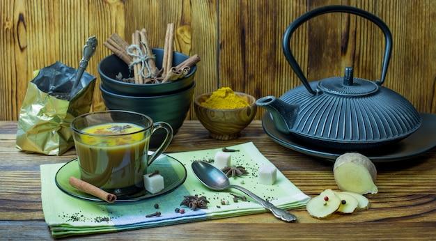料理の材料を使った伝統的なインド茶マサラティーのカップ。木製のテーブルにシナモン、アニス、砂糖、紅茶、コショウ、クローブ、ターメリック。