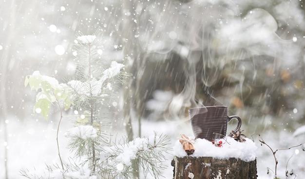 Чашка с горячим напитком в зимнем лесу. горячее какао с корицей на фоне зимнего леса. первый снег и горячий шоколад.