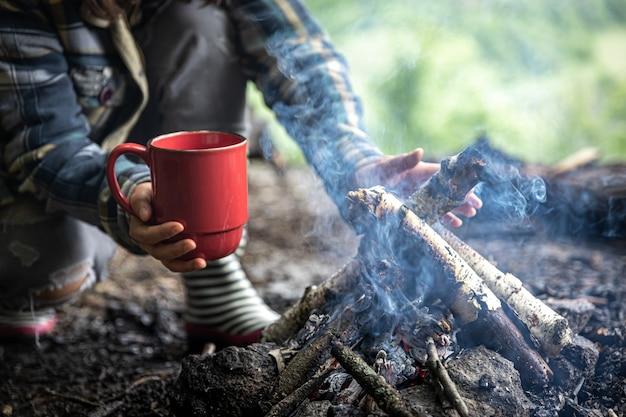 火のそばで森の中をハイキングしながら、温かい飲み物を入れたカップ。