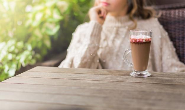코코아와 마시멜로가 든 컵은 앉아 있는 소녀의 배경에 대해 나무 테이블에 서 있습니다. 사진