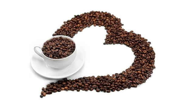コーヒー豆で作られた心の中にコーヒー豆とカップ。コーヒー豆がたくさん。