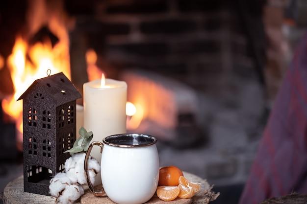 Чашка с декоративными элементами на деревянном пне у камина. концепция деревенского отдыха за городом.