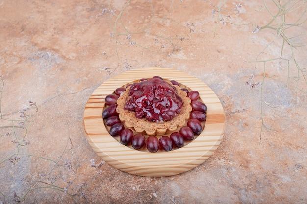 Кекс или тарталетка с соусом из кизила сверху и ягодами кизила вокруг.