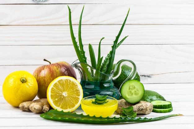 치료 마스크는 주전자에 있고, 알로에, 사과, 생강, 꿀, 레몬, 오이 잎을 흰색 나무 배경에 조작 치료에 적용합니다.