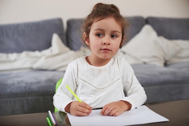 테이블에 앉아 호기심이 아름다운 어린 소녀가 펜을 보유하고 멀리 보인다. 집에서 그리기.