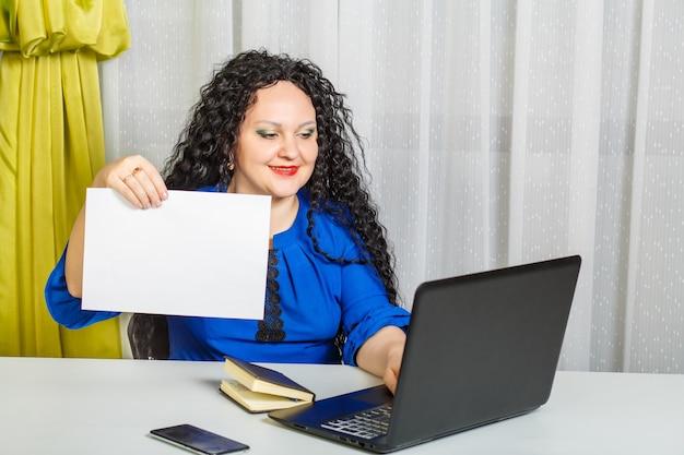 곱슬 갈색 머리 여자는 사무실의 테이블에 앉아 종이에 시트를 보유하고 컴퓨터에 입력합니다. 가로 사진