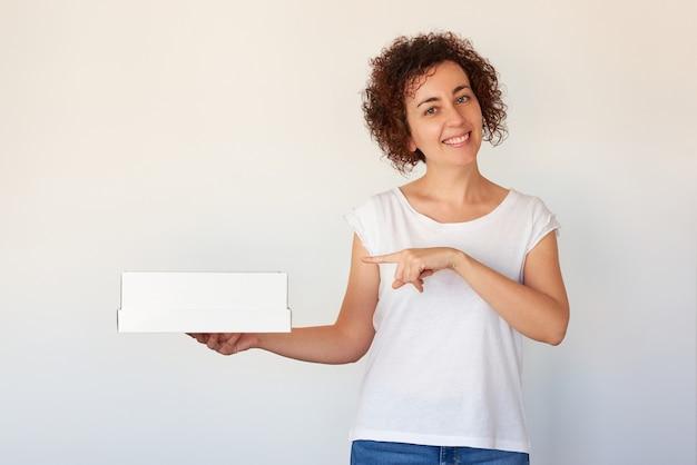 Кудрявая кавказская женщина указывает на белый ящик, улыбаясь в камеру