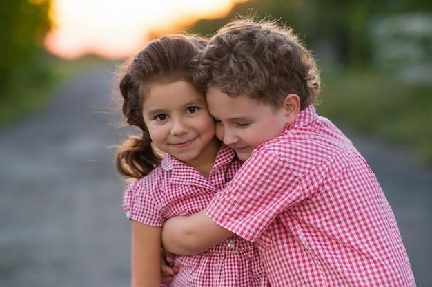 Кудрявая девушка обнимается с кудрявым мальчиком. дети одеты в одном стиле