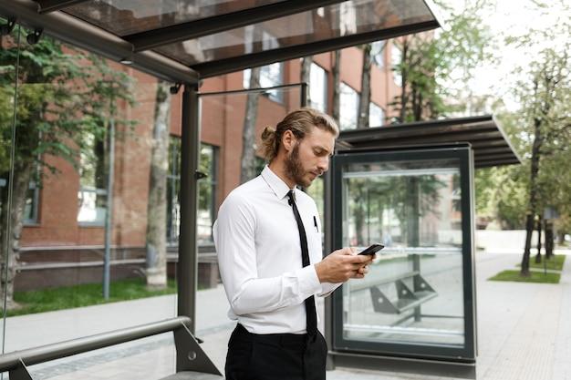 흰 셔츠와 넥타이 차림의 곱슬머리 남자가 버스 정류장에서 버스를 기다리며 전화기를 바라보고 있다. 도시의 교통을 위한 모바일 애플리케이션의 개념.