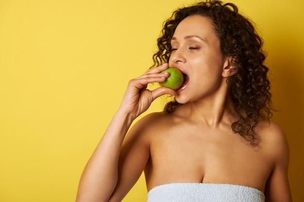 Кудрявая смуглая женщина кусает зеленое яблоко, стоя на желтом фоне.