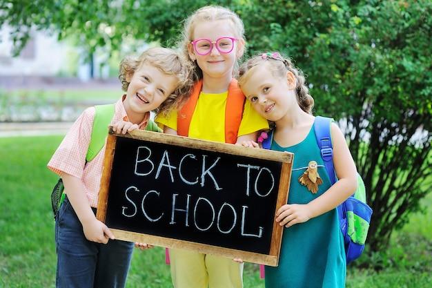 Кудрявый мальчик и две девочки со школьными сумками улыбаются и держат табличку с надписью