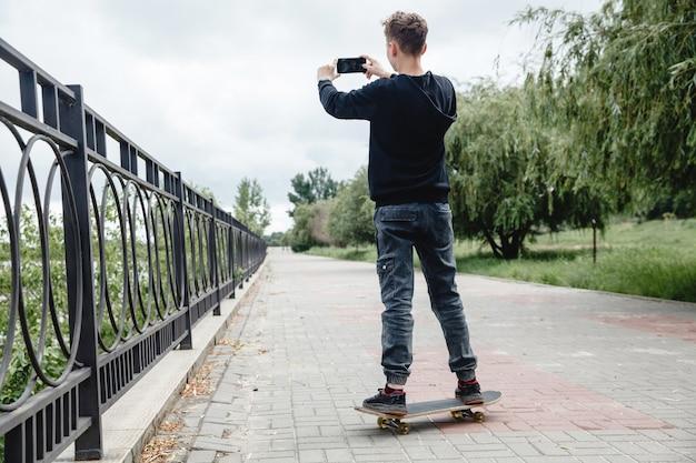 Кучерявый подросток европейской внешности в черной толстовке с капюшоном стоит на скейтборде в переулке ...