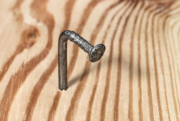 木の板に打ち込まれた湾曲した鉄の釘建設用ファスナーと工具
