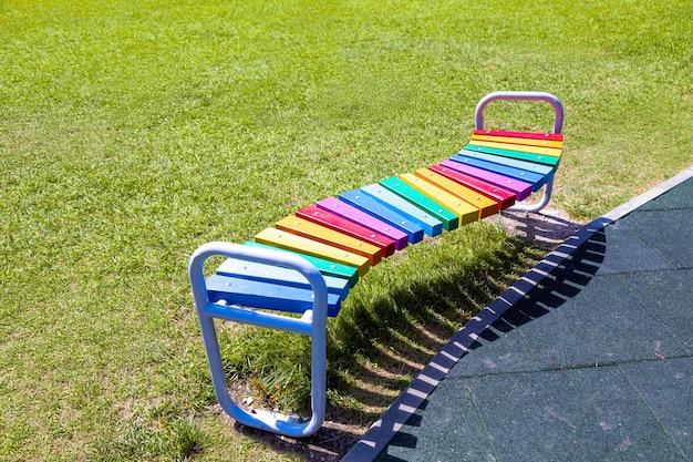 湾曲した木製のベンチは、パブリックガーデンで虹色に塗られています。