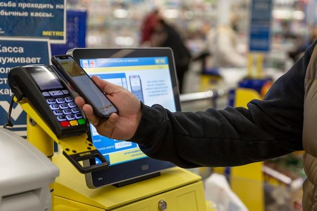 Покупатель в кассе самообслуживания в супермаркете оплачивает покупки кредитной картой.
