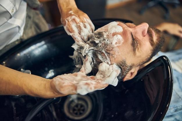 Клиент моет волосы шампунем и моет волосы в хорошо оборудованной парикмахерской