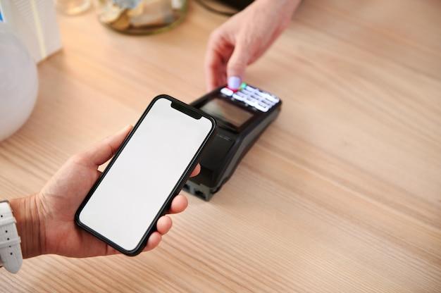 カフェの顧客は、電話のオンラインアプリケーションを使用して非接触型決済を行います。非接触型決済による所有者と顧客の会計のクローズアップ。非接触型決済の概念