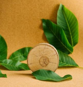 Спил молодого дерева на коричневом фоне с зелеными листьями. естественный фон и текстура.