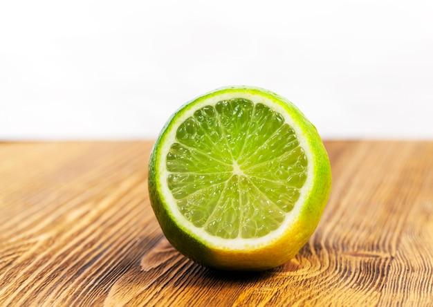 茶色の木製テーブルの上に横たわっている酸っぱい緑のライムのカットピース。写真のクローズアップ。果物に焦点を当てる