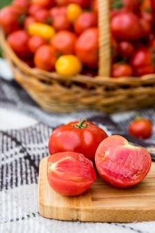 厚板にカットしたトマト。秋までに収穫。トマトの大きなバスケットを背景に。