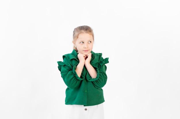 かわいい8歳の女の子が立って、あごの下で両手で見える