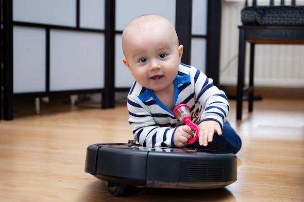 귀여운 사랑스러운 아기가 한 손에 아기 딸랑이와 함께 집에서 로봇 진공 청소기를 타고있다