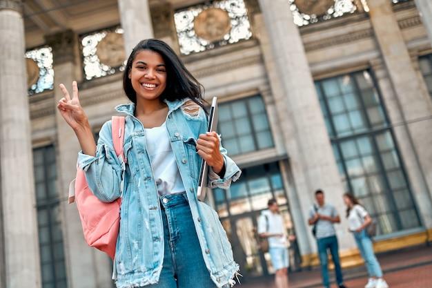 Симпатичная афроамериканка-студентка демонстрирует победный жест с рюкзаком и ноутбуком возле кампуса на фоне группы студентов.