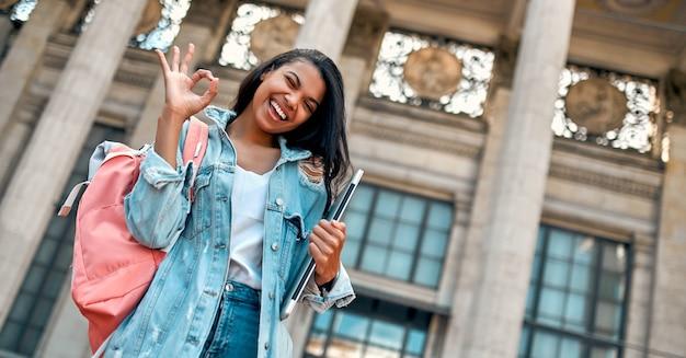 귀여운 아프리카계 미국인 여학생이 한 무리의 학생들을 배경으로 캠퍼스 근처에서 배낭과 노트북을 들고