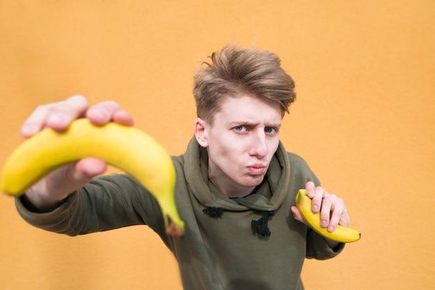 Милый и забавный молодой человек с бананами в руках позирует на оранжевой стене с бананами в руках