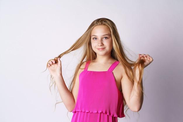 흰 벽에 분홍색 옷을 입은 백인 외모의 귀엽고 행복한 소녀가 그녀의 긴 머리로 활약