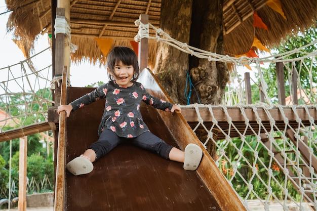 Милая азиатская маленькая девочка очень счастлива, играя слайды на детской площадке