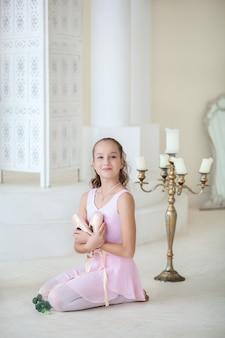 ピンクのバレエ衣装を着たかわいいバレリーナが、ポワントを手に床に座って笑っています。ダンスクラスの女の子。女の子はバレエを勉強しています。クラシックバレエ、ダンス。バレエスタジオ。