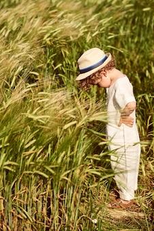 Милый красивый мальчик, одетый в льняной тканью и белой шляпе, стоя в поле зеленой пшеницы