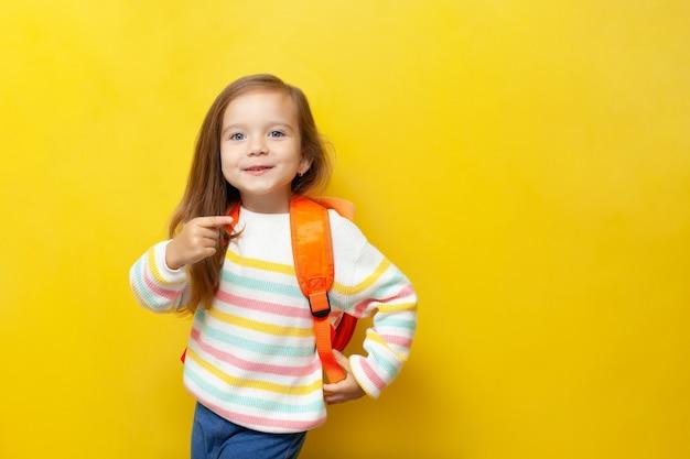 파란 눈과 배낭을 가진 귀여운 아름다운 소녀가 그녀의 손가락을 옆으로 가리킵니다. 노란색