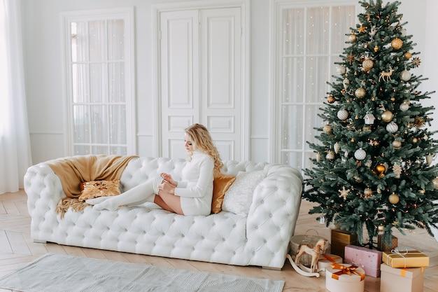 Милая красивая счастливая молодая женщина в платье расслабляется, сидя на белом диване