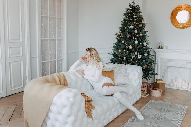 Милая красивая счастливая молодая женщина в вязаном платье отдыхает, сидя на белом диване